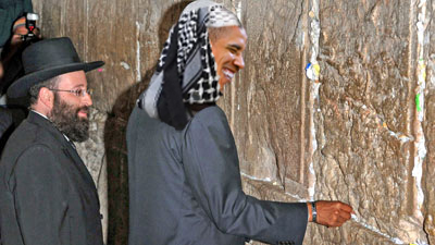 JERUSALEM, ISRAEL - JULY 24: In this handout photo provided by the Ministry of Foreign Affairs (MFA), presumptive Democratic presidential candidate Sen. Barack Obama (D-IL) places a note between the ancient stones  of the Western Wall, as the rabbi of the holy place Shmuel Rabinowitz looks on, before dawn July 24, 2008 in Jerusalem's Old City. Obama visited Judaism holiest site after a day in Israel and the West Bank and before taking off for Germany. (Photo by Avi Hayon/MFA via Getty Images) *** Local Caption *** Barack Obama;Shmuel Rabinowitz