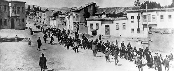 Armenian civilians, escorted by armed Ottoman soldiers, are marched through Mamüret-ül Aziz, (today Elâzığ), known as Kharpert by Armenians, to a prison in the nearby Mezireh district, April 1915