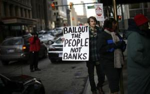 """A man joins a protest organized by a group called """"Moratorium Now"""" in front of the Bank of America building in downtown Detroit."""