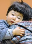 A young evacuee from vincity of Tokyo Electric Power Co.'s Fukushima Nuclear Plant shows fatigue at a evacuation shelter in Kawamata, Fukushima Prefecture Sunday March 13, 2011. (AP Photo/Kyodo News) JAPAN OUT, MANDATORY CREDIT, NO SALES IN CHINA, HONG KONG, JAPAN, SOUTH KOREA AND FRANCE