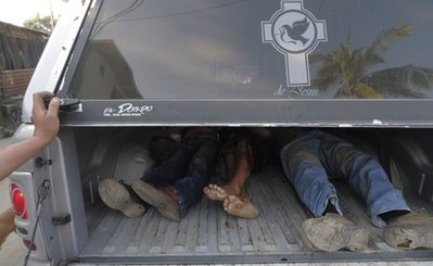 The bodies of three men lie together after being placed in the back of a funeral home's pick-up truck after they were killed by unidentified gunmen in the Pacific resort city of Acapulco, Mexico, Sunday Dec. 5, 2010. At least 11 men have been killed this weekend as authorities say the battle for control of a fractured drug cartel is responsible for the rising violence in Acapulco. (AP Photo/Bernandino Hernandez)