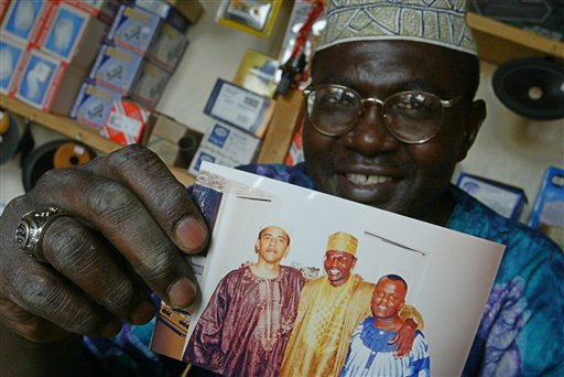 FILE - This Tuesday, Sept. 14, 2004 file photo shows Malik Obama, the older brother of  US President Barack Obama, who holds an undated picture of Barak, left, and himself, center, and an unidentified friend in his shop in Siaya, eastern Kenya. President Barack Obama's polygamist half brother in Kenya has married a woman who is more than 30 years younger than him. The 19-year-old's mother told The Associated Press on Friday Oct. 15, 2010 she is furious that her daughter quit high school and married the 52-year-old. Malik Obama, who is Muslim, has two other wives. Polygamy is legal in Kenya if it falls under religious or cultural traditions.  (AP Photo/Karel Prinsloo)