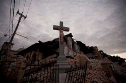 A cross stands intact in front of a church that collapsed during Tuesday's earthquake at the Canape Vert neighborhood in Port-au-Prince, Thursday, Jan. 14, 2010. (AP Photo/Ramon Espinosa)