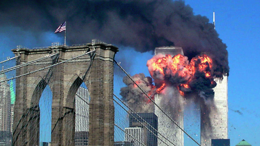USA - YEAREND PICTURES 2001 - With the Brooklyn bridge in the foreground, a plane explodes after hitting the second tower of the World Trade Center as the other tower burns, in New York September 11, 2001. Both towers of the complex collapsed after hijacked planes hit them.  REUTERS/Sara K. Schwittek --- Image by © Reuters/CORBIS