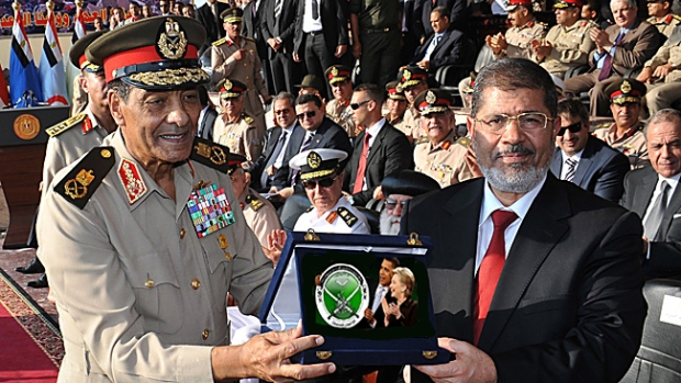 """29/06/2012 WIRE: In this handout picture made available by the Egyptian presidency on June 30, 2012, (L to R) military council chief Field Marshal Hussein Tantawi (L), presents the """"shield of the Armed Forces"""" the Egyptian military's highest honor to President Mohamed Morsi (R) during a ceremony at a military base in of Cairo.  Morsi was sworn in as Egypt's first freely elected civilian president on Saturday and formally received a transfer of power and pledge of support from the military, which has ruled since last year.  AFP PHOTO / HO ==RESTRICTED TO EDITORIAL USE - MANDATORY CREDIT """"AFP PHOTO /EGYPTIAN PRESIDENCY """" - NO MARKETING NO ADVERTISING CAMPAIGNS - DISTRIBUTED AS A SERVICE TO CLIENTS=="""