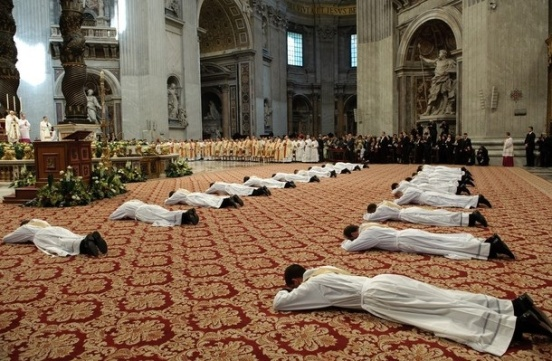 New priests lie in front of Pope Benedict XVI (L) during a mass for the ordination of new priests at St. Peter Basilica at the Vatican. AFP PHOTO / VINCENZO PINTO