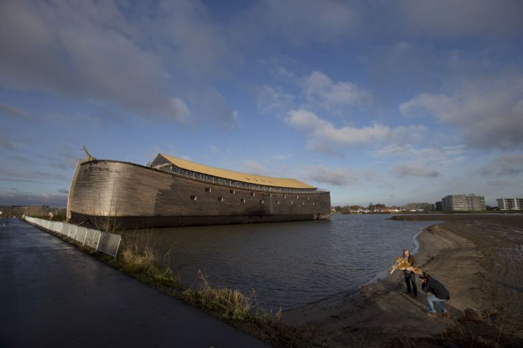 Johan Huibers, bottom right, poses, after being asked by a photographer to go outside, with a stuffed tiger in front of the full scale replica of Noahís Ark in Dordrecht, Netherlands, Monday Dec. 10, 2012. (AP Photo/Peter Dejong)