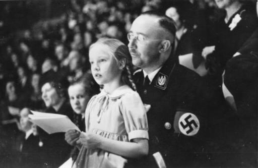 Reichsfuehrer-SS Heinrich Himmler holding his daughter Gudrun while seated in an audience.