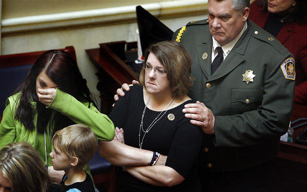 Kane County Sheriff Lamont Smith, right, comforts Shawna Harris and her daughters Kirsten, 14, and Kristina, 10, on Wednesday. State legislators held a moment of silence Wednesday for three Utah Sheriff officers killed in the line of duty last year.Laura Seitz, Deseret News