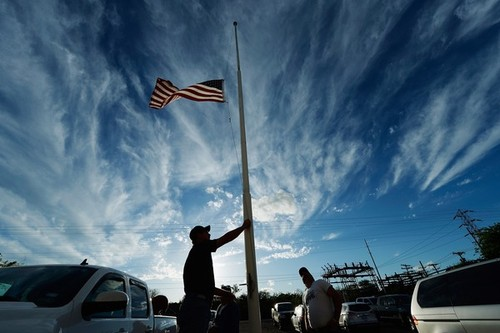 WEST, TX - APRIL 18:  Bill Warren, a member of Veterans of Foreign Wars Post 4819, lowers the U.S. flag to half staff in memory of victims of the West Fertilizer Company explosion April 18, 2013 about 20 miles north of Waco in West, Texas. A fiery explosion that damaged or destroyed buildings within a half-mile radius ripped through the facility last night, injuring more than 160 people and killing an unknown number of others.  (Photo by Kevork Djansezian/Getty Images)