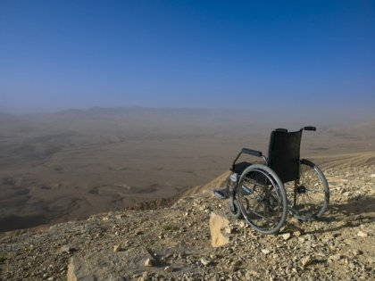 Empty wheelchair on cliff edge, desert