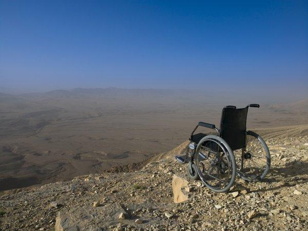 Empty wheelchair on cliff edge, desert