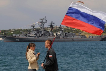 A man holding a Russian flag speaks with a girl wearing a telnyashka, a traditional navy sailor's striped vest, under her jacket during a naval parade to mark the 225th anniversary of Russian navy's Black Sea fleet at the Crimean Peninsula port of Sevastopol, Ukraine, Sunday, May 11, 2008, with the Russian Smetlivy destroyer in the background.(AP Photo/Sergei Chuzavkov)
