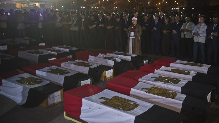 Egyptian army and security officers pray over coffins covered with the national flags at Almaza military Airbase in Cairo during a funeral for 25 policemen murdered by Obama's Muslim Brotherhood. There is also growing concern in Egypt that the same scenario is taking place in Syria to install them there by the banking cabal to do their bidding.