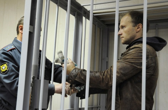 The photographer Denis Sinyakov (right) chareged with an illegal attempt at penetrating the Prirazlomnaya oil platform, is seen before hearings on his pre-trail detention measure at the Leninsky Court, Murmansk. (RIA Novosti/Sergey Eshenko)