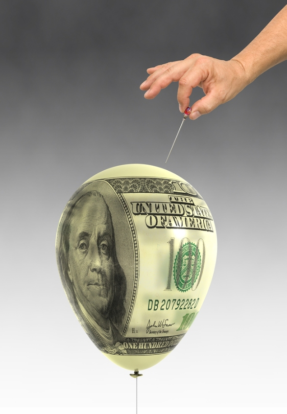 Orchestrated balloon printed with a dollar bills about to be popped.