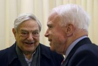 Chairman of Soros Fund Management George Soros, left, talks with U.S. Senator John McCain, right, during the World Economic Forum in Davos, Switzerland, Thursday, Jan. 23, 2014.. (AP Photo/Michel Euler)