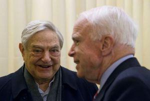 Chairman of Soros Fund Management George Soros, left, talks with U.S. Senator John McCain, right, during the World Economic Forum in Davos, Switzerland, Thursday, Jan. 23, 2014.. (AP Photo/Michel Euler)