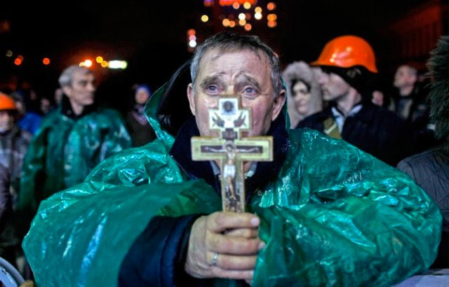 """Ukraine Christian holds a crucifix as he prays in Kiev, Ukraine, Thursday, Feb. 20, 2014   The deposed President vowed to defeat """"terrorists"""" responsible for seizing weapons and burning down buildings. AP Photo/ Marko Drobnjakovic"""