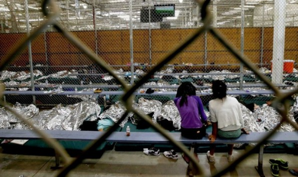 Two young girls watch a World Cup soccer match on a television from their holding area where hundreds of mostly Central American immigrant children are being processed and held at the U.S. Customs and Border Protection Nogales Placement Center in Nogales, Arizona.