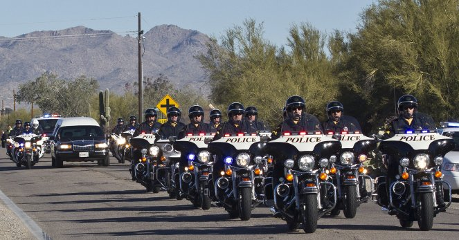 the remains of U.S. District Judge John Roll arrives at the St. Elizabeth Ann Seton Church before his funeral on Friday, Jan. 14, 2011, in Tucson, Ariz.
