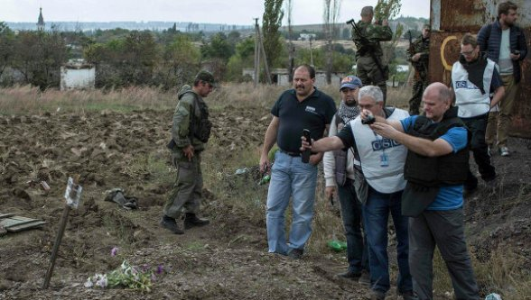OSCE observers at a mass burial site in the village of Nizhnaya Krynka.