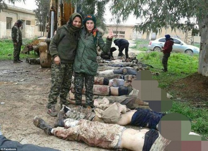 Sunni YPG soldiers smiling, in front of rows of dead ISIS bodies.