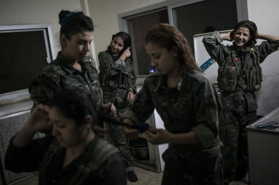 Young YPJ recruits Fix their hair at 4:30 AM before participating in training exercises and drills, near Derek City, Syria.