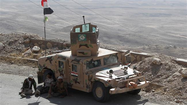 Iraqi fighters from the Popular Mobilization units, fighting alongside Iraqi forces, sit next to an armored vehicle during a military operation against Daesh militants in Makhoul Mountains, north of Baiji, on October 17, 2015. © AFP