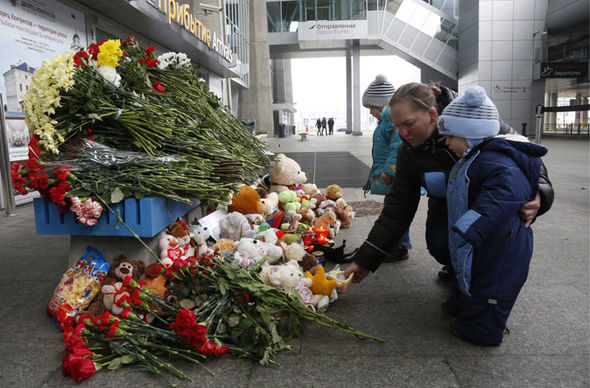 People lay flowers and toys at an entrance of Pulkovo airport.