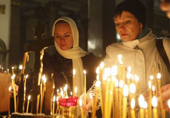 People light candles inside an Orthodox church in St Petersburg