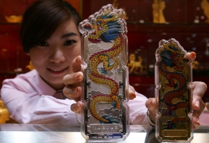 An employee shows off silver and gold bullion bars engraved with dragons at a gold shop in Beijing.