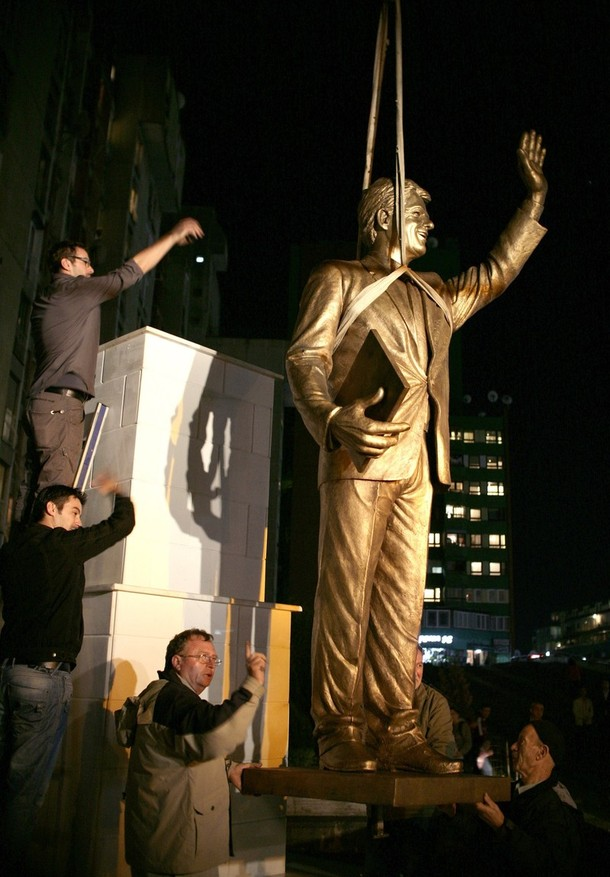 Workers install a monument to former U.S. President Bill Clinton on Bill Clinton Boulevard in Pristina